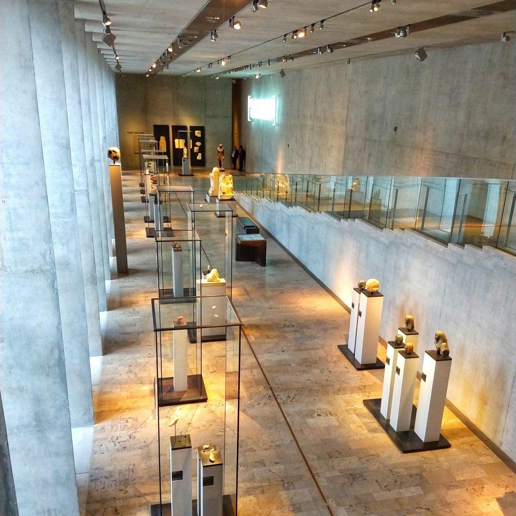 Blick in den Raum Kunst und Form des Ägyptischen Museums München. Linkerhand dreieckige Pfeiler aus Beton. Rechts führt eine Treppe auf die Ausstellungsebene. Dort stehen altägyptische Statuen in Glasvitrinen und auf Sockeln.