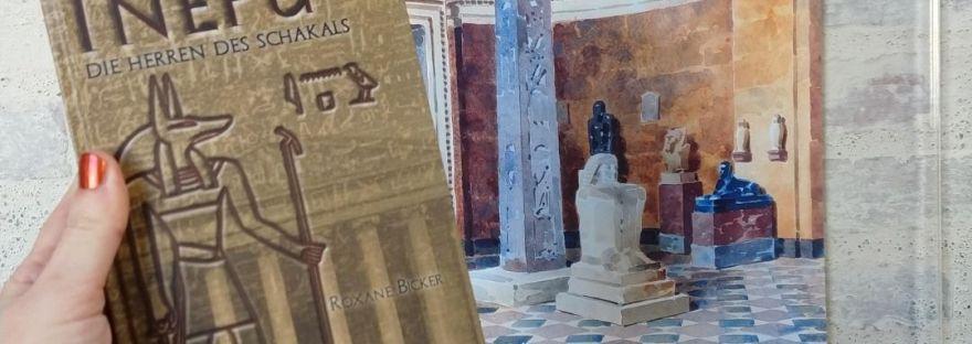 Eine Hand hält das Buch Inepu. Im Hintergrund eine Auquarellzeichnung der historischen Räume der Glyptothek.