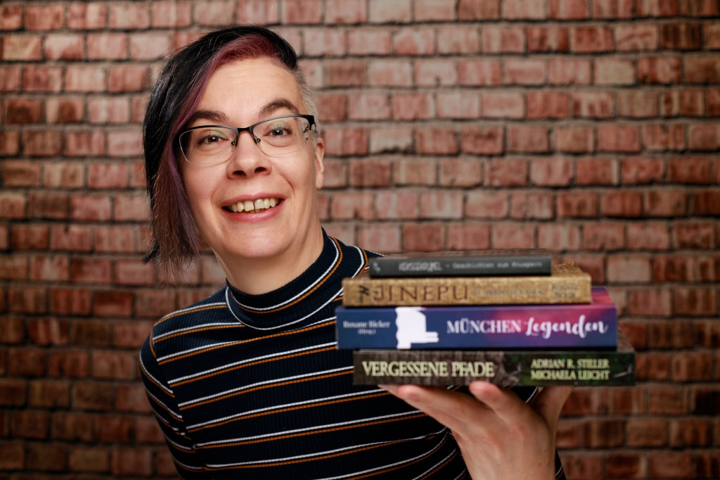 Lachen hält Roxane vier Bücher ins Bild